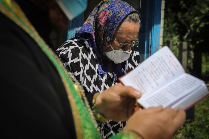 Preot ortodox în timpul unei vizite la o enoriașă