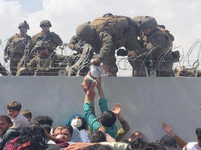 Bebelus trecut peste gardul de sârmă ghimpată în aeroportul din Kabul