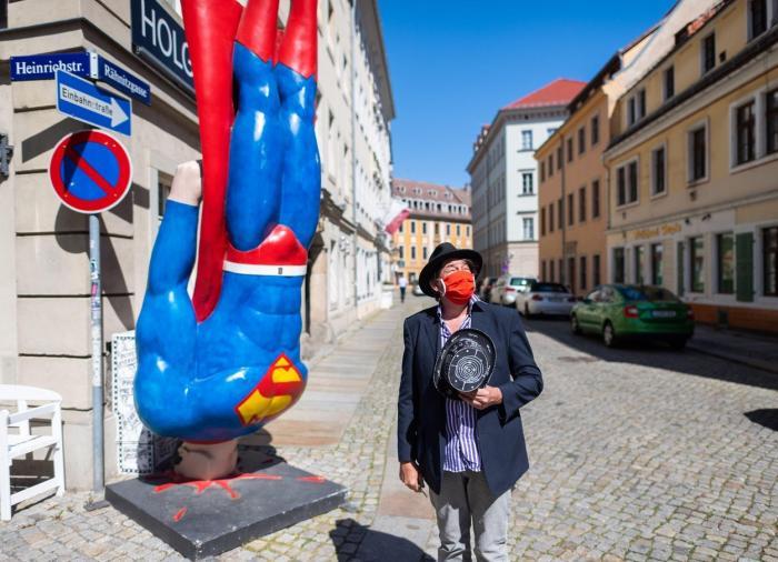Artistul Holger stă în faţa galeriei sale din Dresda alături de statuia lui Superman realizată de Marcus Witwers