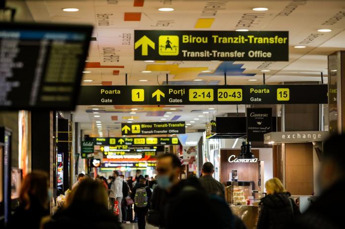 Persoane cu mască de protecție pe aeroportul Otopeni