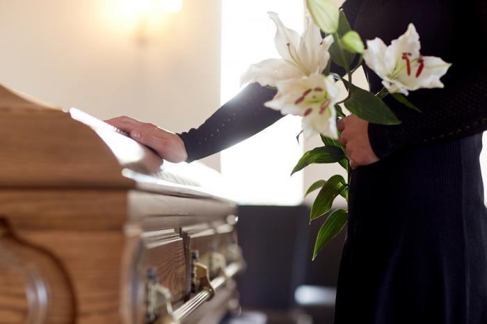 În imagine: O femeie cu flori albe în mână, lângă un sicriu