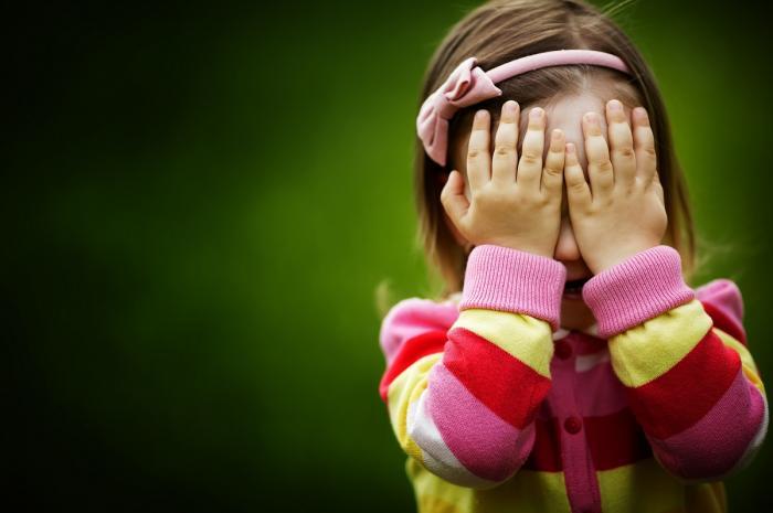 Fetiţă îmbrăcată în roz, cu mâinile la ochi
