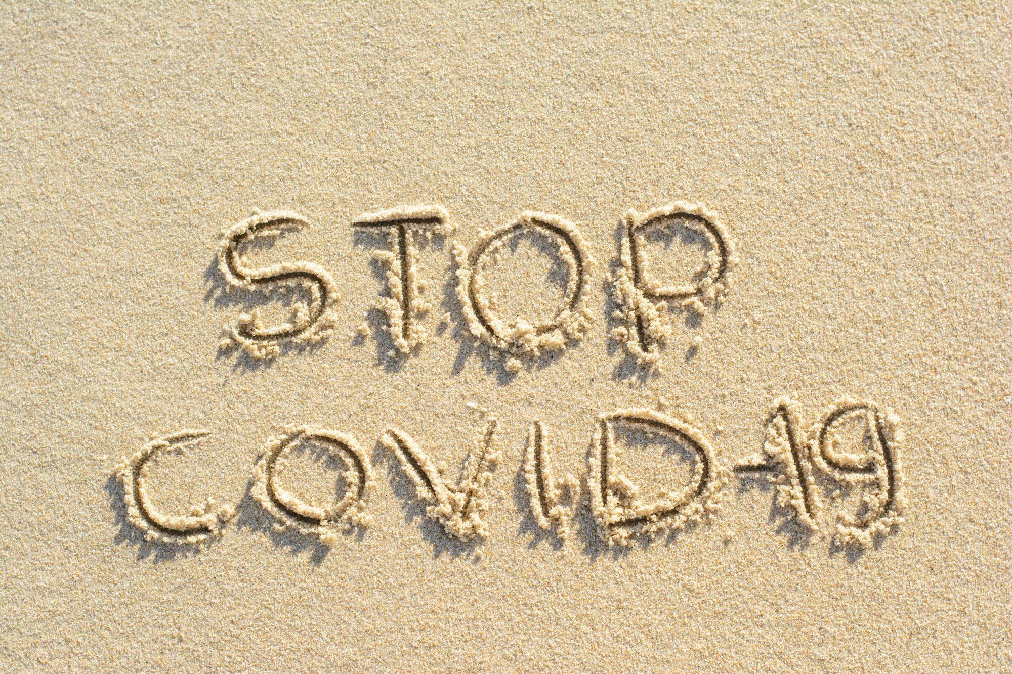 Mesaj Stop Covid-19 scris pe nisip