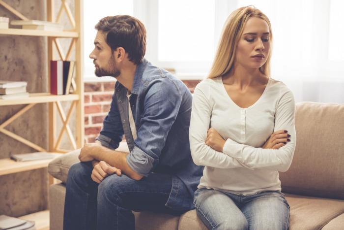 O femeie şi un bărbat stau supăraţi unul pe celălalt după o ceartă