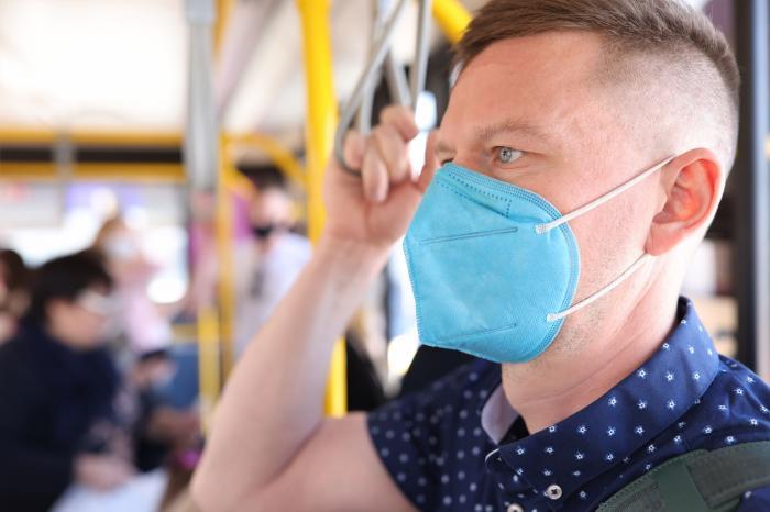 Un bărbat cu mască de protecție într-un autobuz
