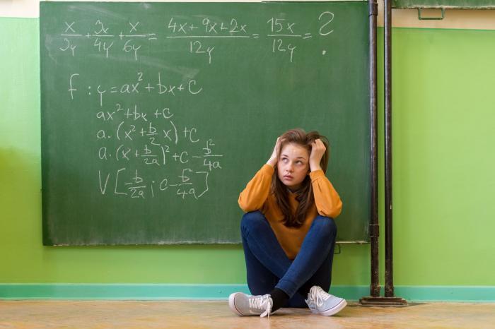 O fată stă pe gânduri cu spatele la o tablă pe care sunt scrise câteva ecuații de matematică