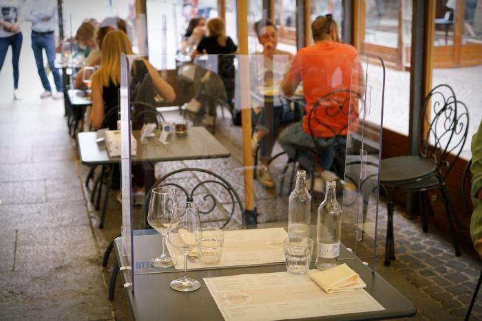 Persoane care mănâncă la un restaurant în care sunt respectate reguli de prevenire a răspândirii Covid-19