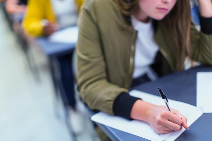 O tânără susține un examen într-o sală de clasă