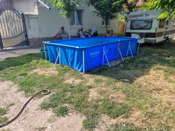 Locuitorii dintr-un sat din Timiş, inventivi şi economi: Şi-au scos piscinele în faţa caselor şi le-au umplut cu apă de la cişmeaua publică