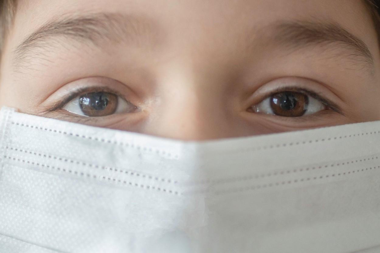 Copil cu masca de protectie pe fata
