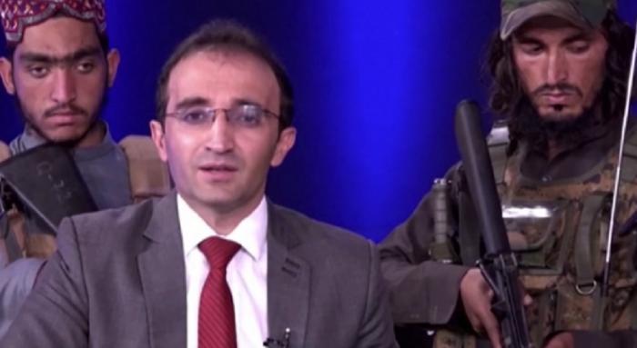 Un prezentator TV afgan, înconjurat de opt talibani înarmați, transmite un mesaj populației. Militanții au dat buzna în platou cu puști de asalt