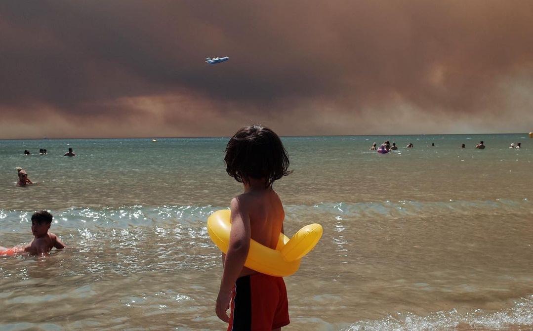 un băiețel de pe plajă se uită la infernul dezlănțuit