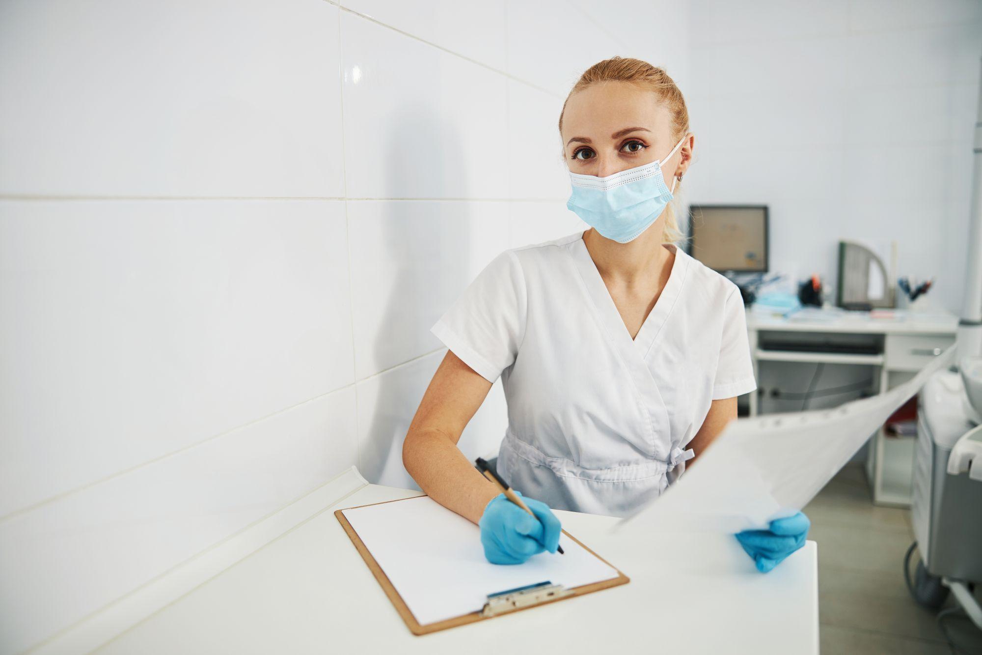 O doctoriţă cu mască de protecţie stă pe scaun şi notează într-un raport
