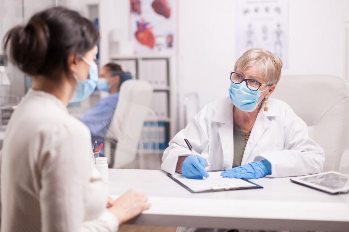Un angajat din sistemul medical noteză datele unei persoane, în contextul pandemiei Covid