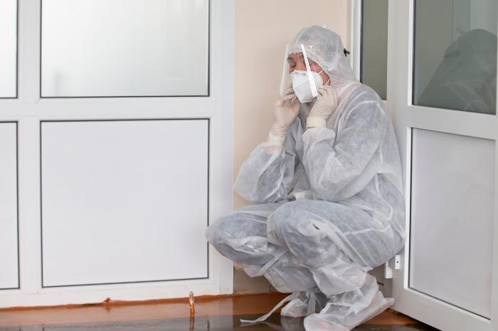 Un medic, extenuat în haine de protecţie, în timpul pandemiei de coronavirus