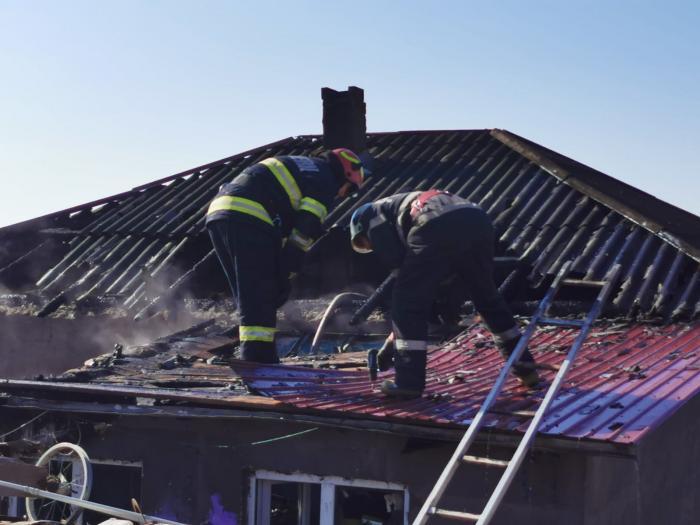 Pompierii ISU Botoșani intervin la stingerea incendiului care le-a cuprins casa celor doi frați din Roșiori