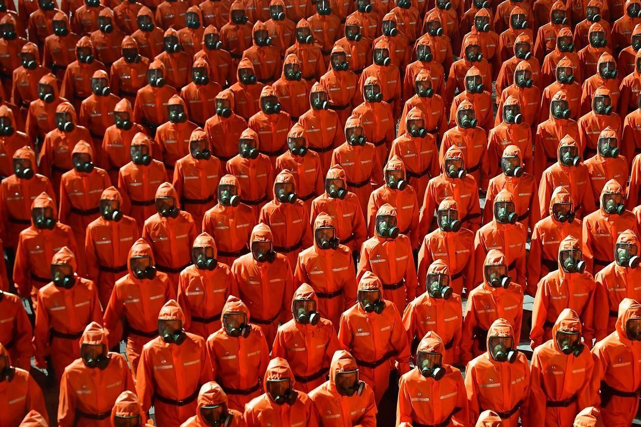 Parada de la miezul nopţii. Coreea de Nord nu şi-a mai prezentat rachetele, dar a defilat cu oameni îmbrăcaţi în costume de protecţie | GALERIE FOTO
