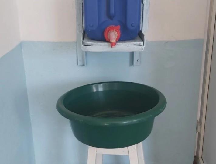 Un bidon şi un lighean pus pe un scaun, în loc de chiuvetă, într-o școală din Vrancea. Peste 250 de școli din țară nu pot asigura măsuri igienico-sanitare minime