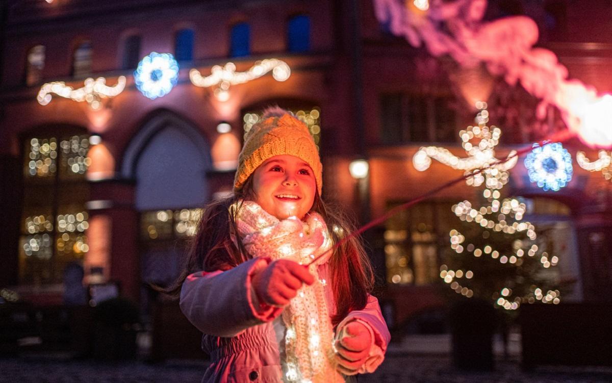 Fetiţă lângă decoraţiuni de Crăciun