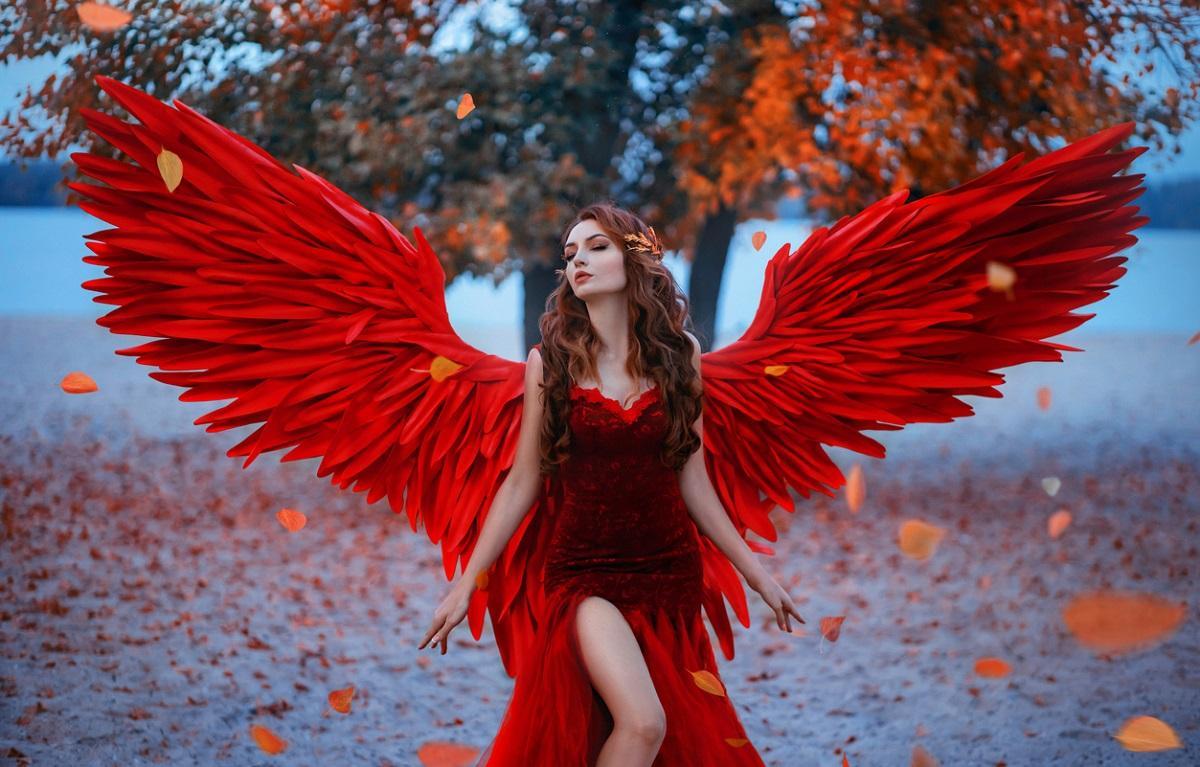 Tânără îmbrăcată în rochie roşie, purtând aripi din pene roşii