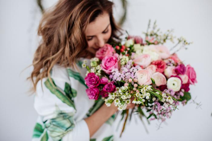 O femeie admiră un buchet spectaculos de flori