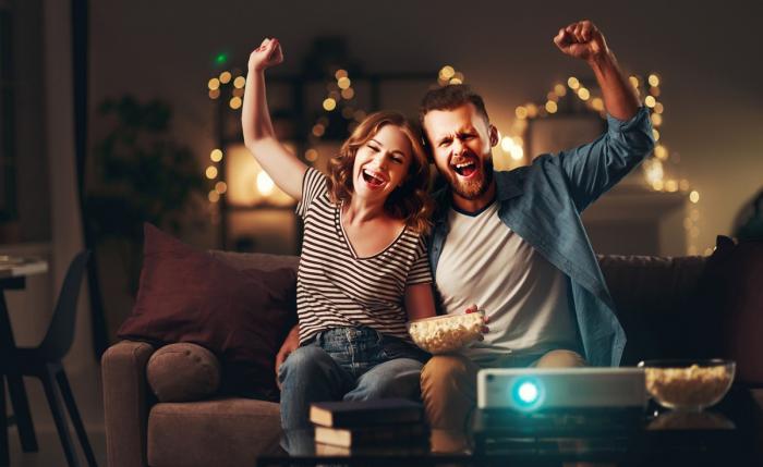 Doi tineri se pregătesc să se uite la un film, cu popcorn pe masă