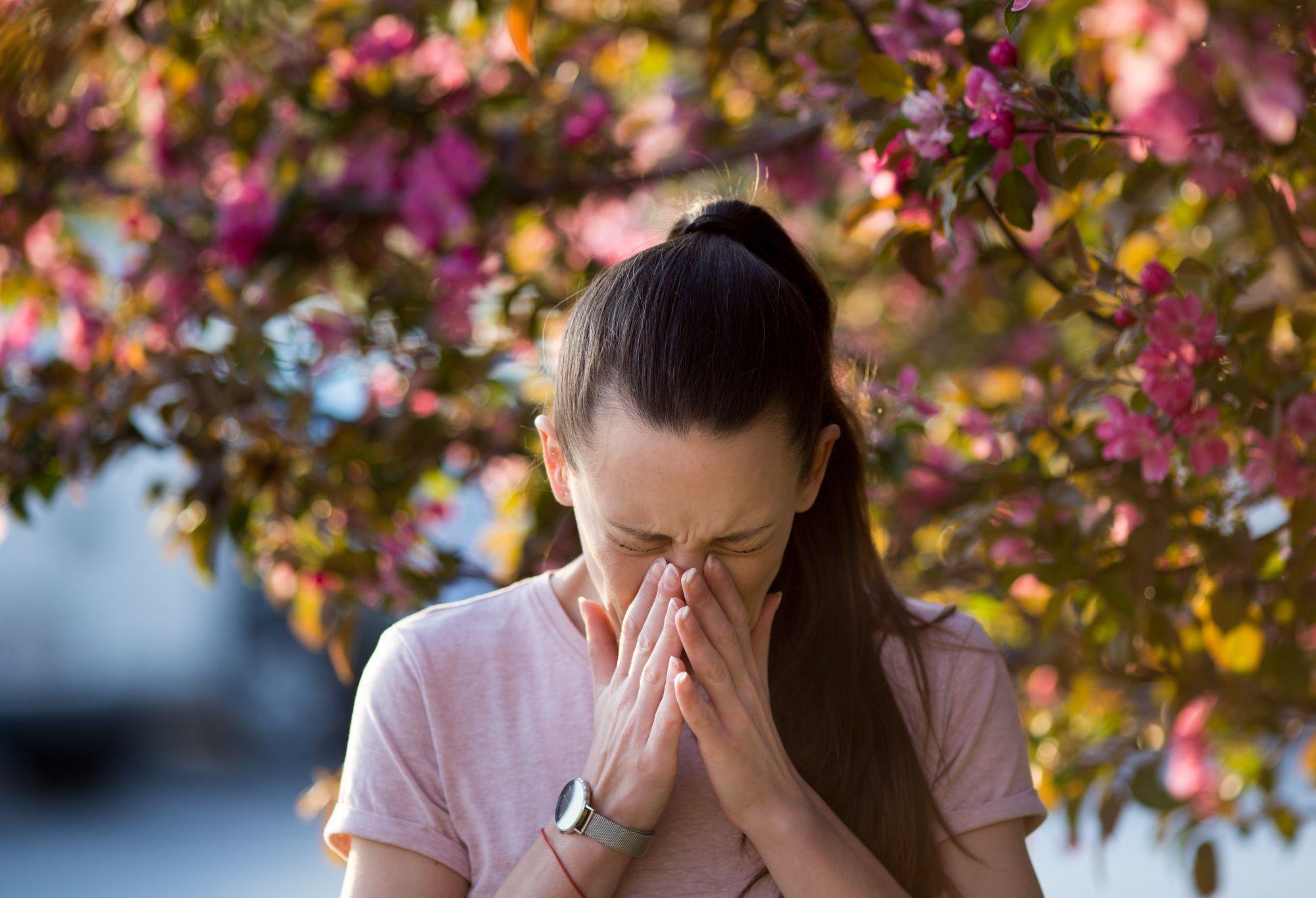 O femeie tânără strănută în fața unui copac înflorit, având alergie la polen