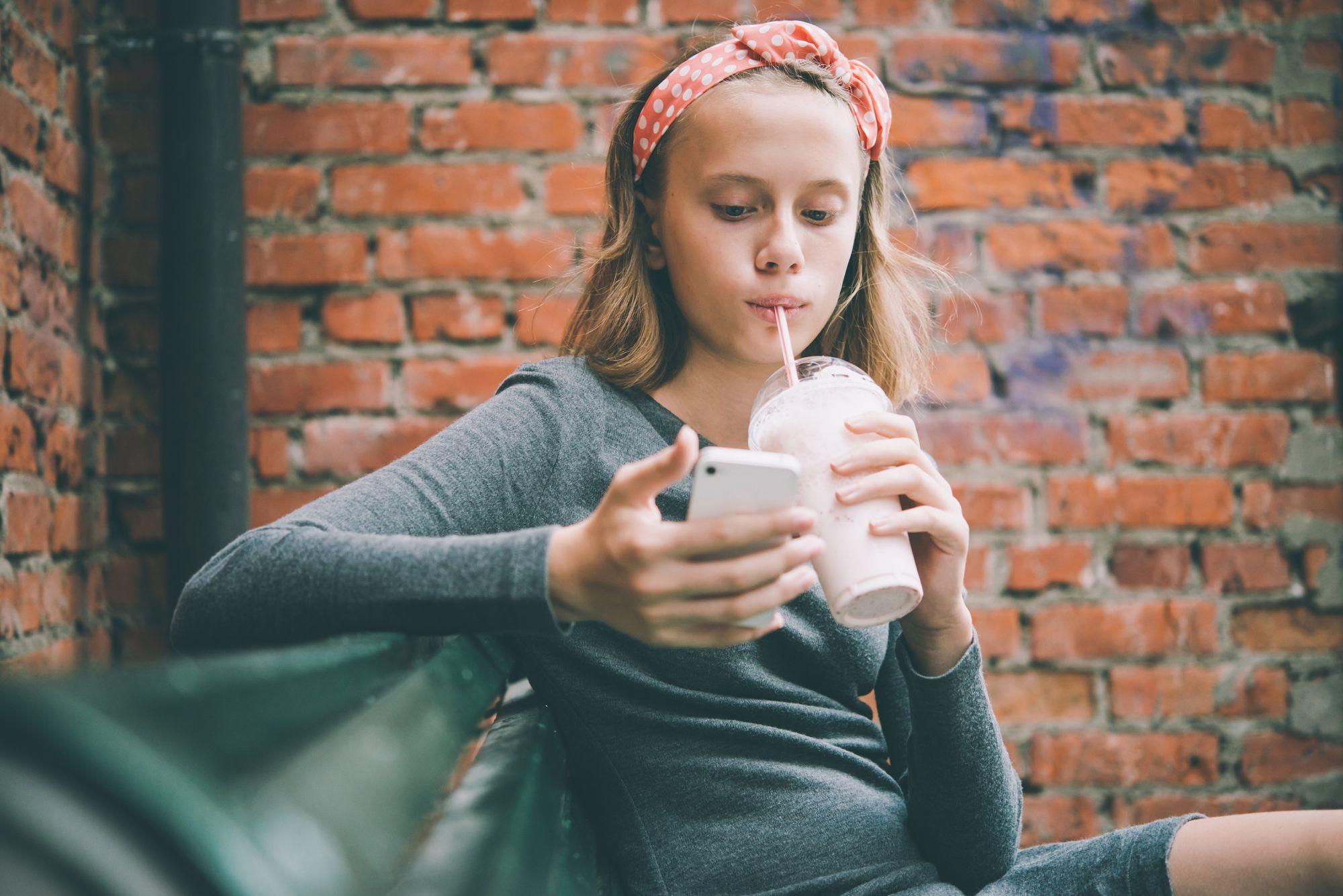 O tânără îşi foloseşte telefonul mobil în timp ce bea cu paiul dintr-o băutură răcoritoare