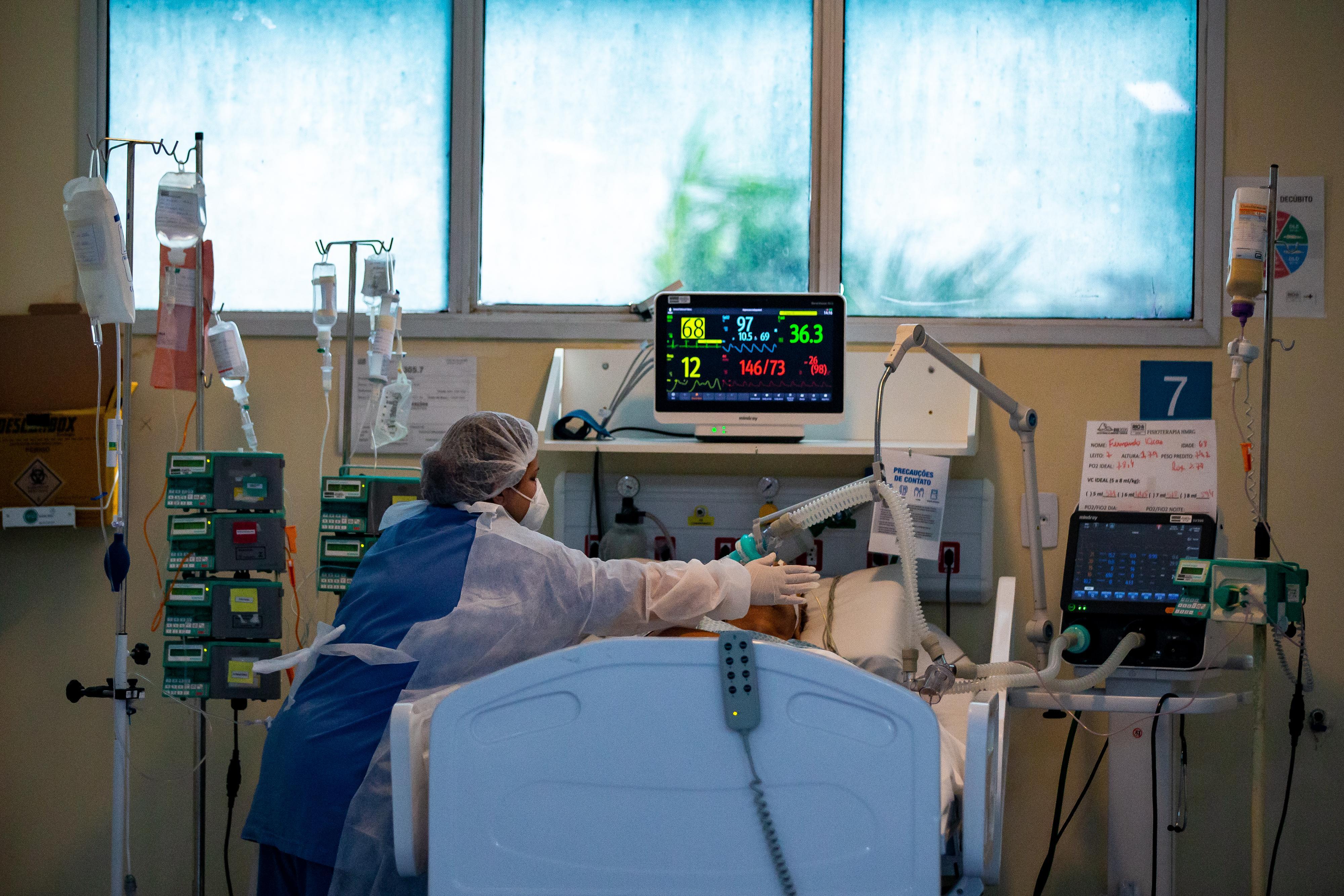 O asistentă îngrijește un pacient infectat cu Covid-19, pe secția de terapie intensivă