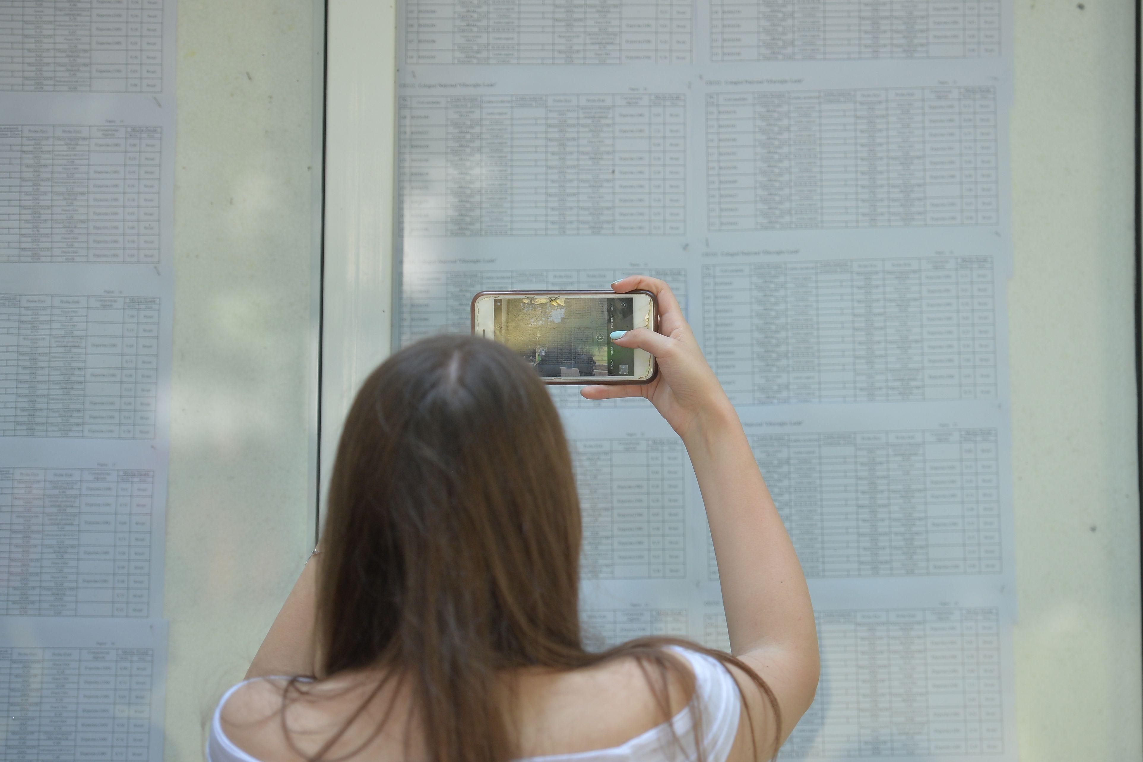 O elevă fotografiază rezultatele examenului