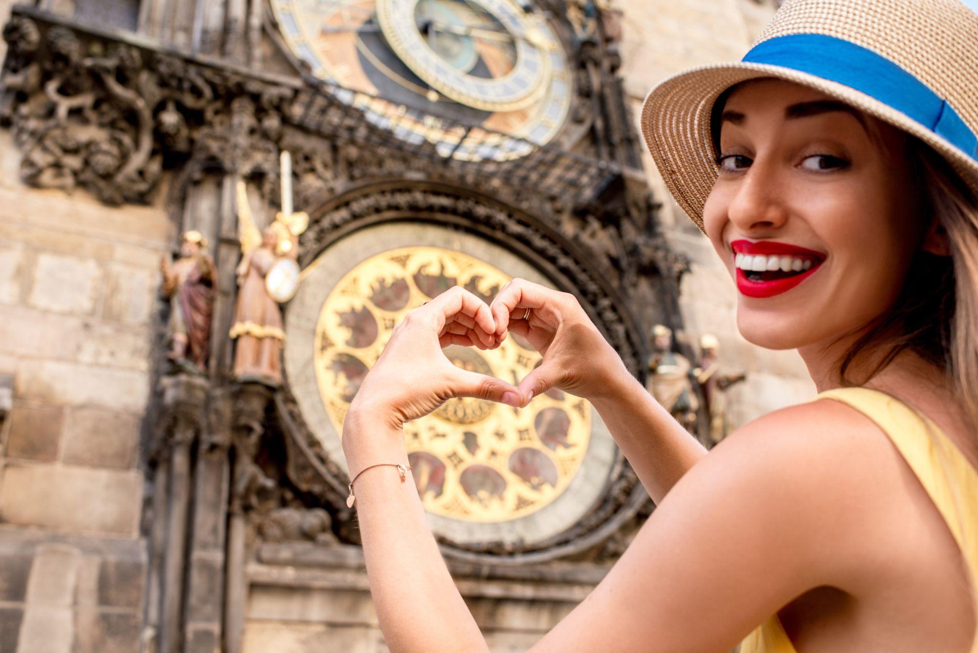 O tânără face forma inimii din degete în dreptul ceasului astrologic din Praga