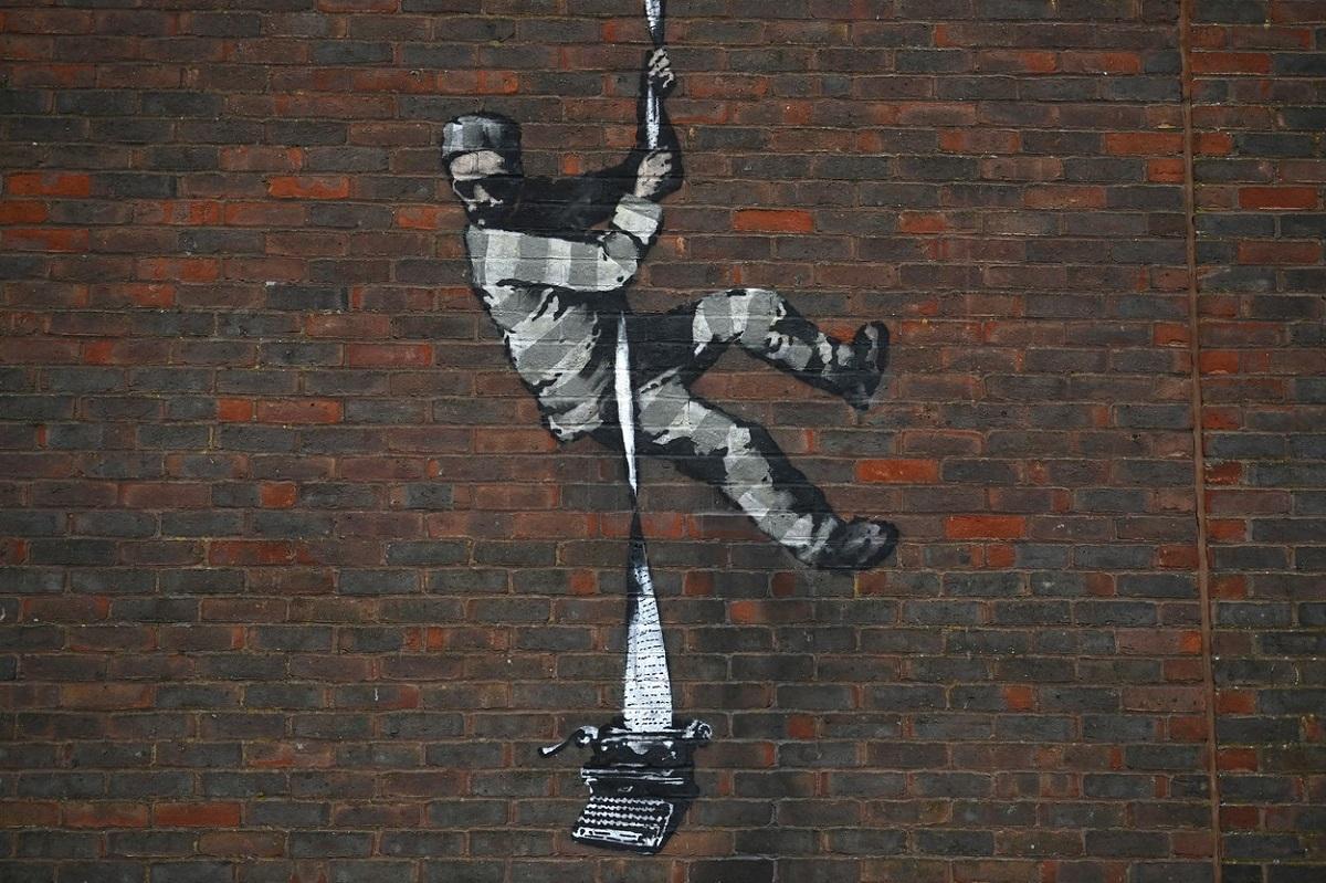 Lucrarea arată un prizonier care scapă folosind o frânghie din foi legate de o mașină de scris