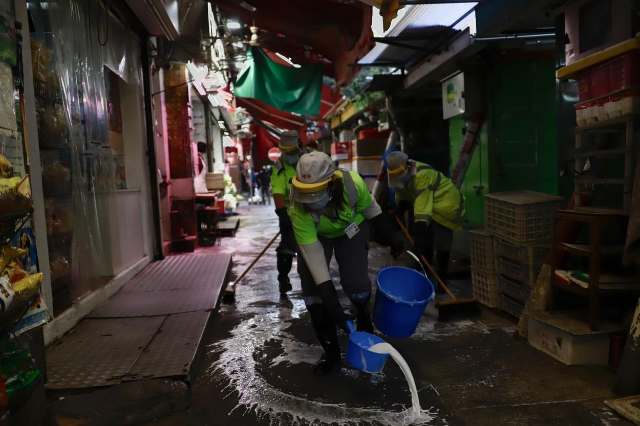 Fotografie dintr-o piață din China. Muncitorii dezinfectează zona
