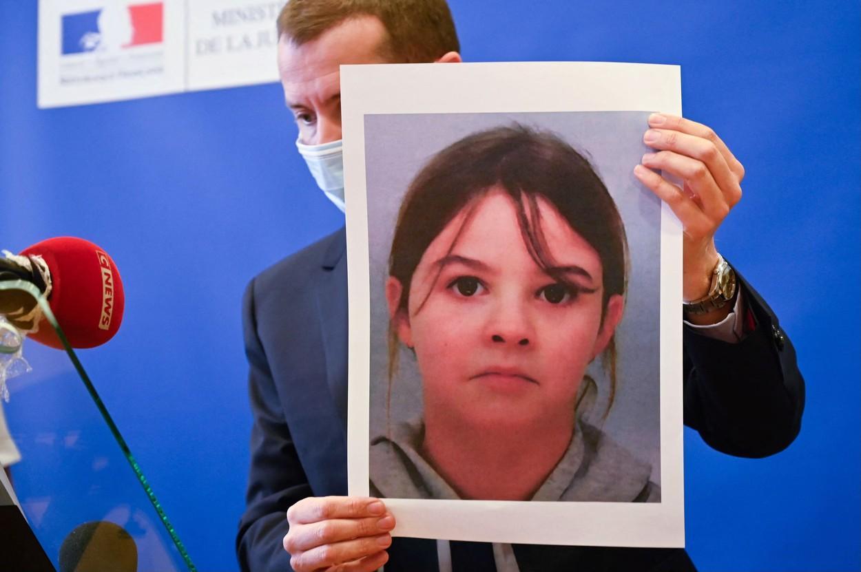 Un prolițist prezintă fotografia fetiței răpite