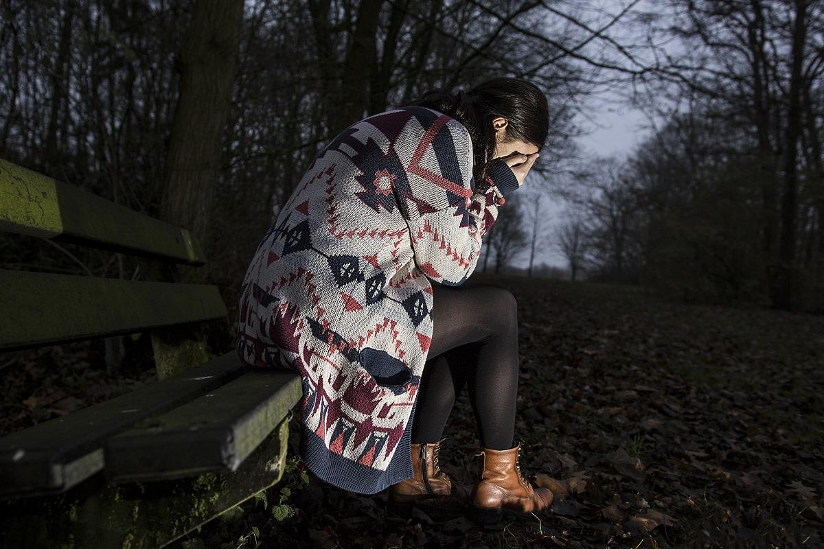 O tânără femeie cu un pulover lung, așezată pe o bancă într-o pădure, în amurg. Ea își acoperă ochii în timp ce plânge