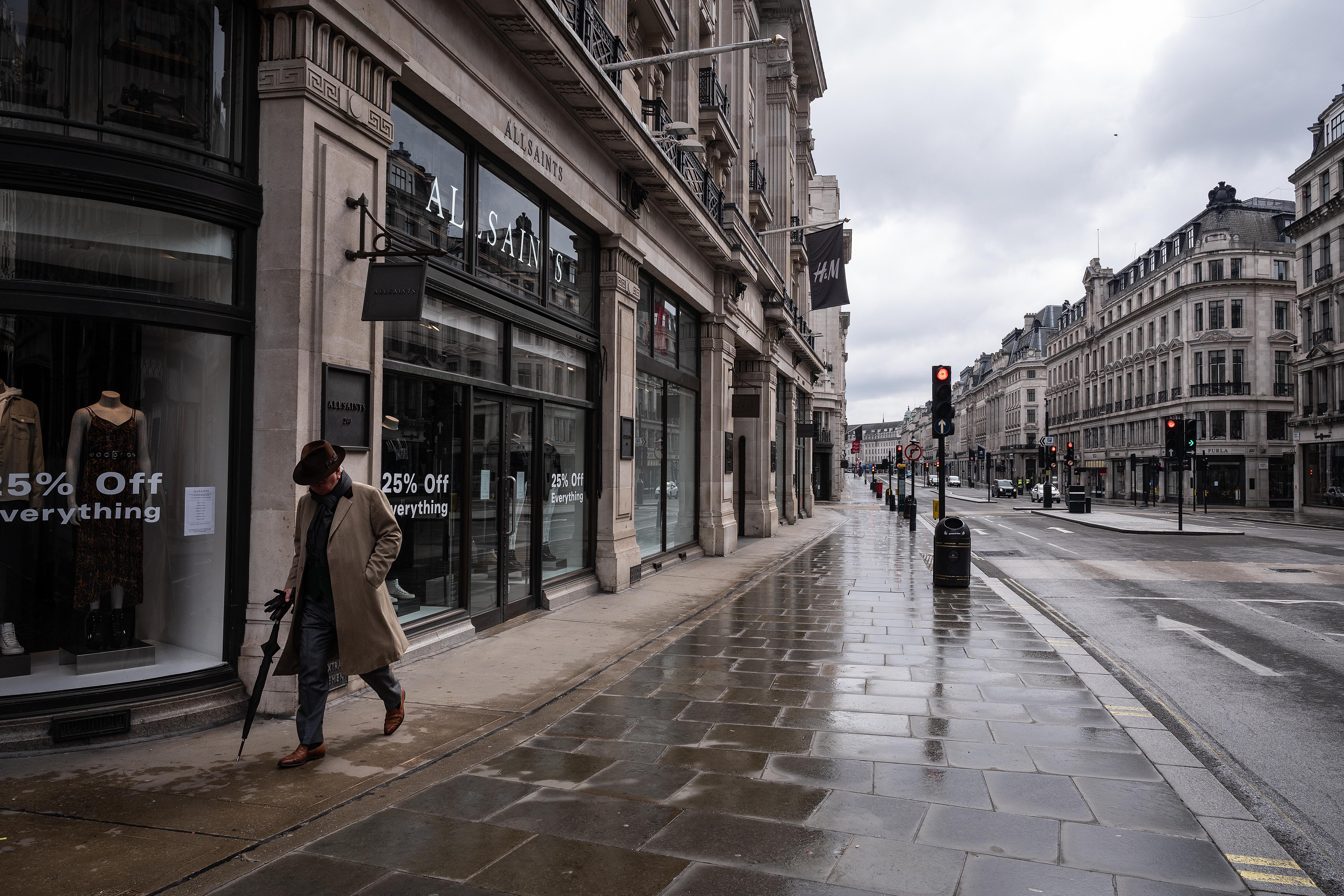 Un bărbat pășeste pe Regent Street din Londra, prin fața magazinelor închise