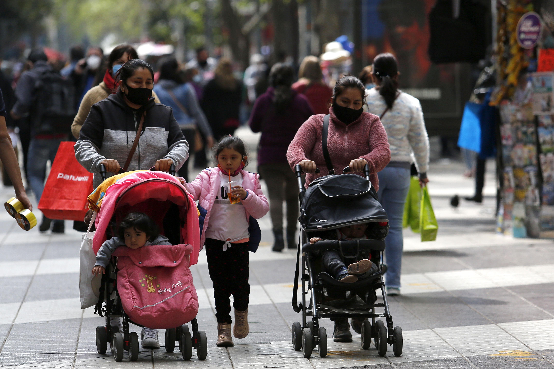 Mai multe mame purtând măști de protecție își plimbă copiii în centrul orașului Santiago, Chile