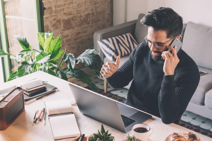 Un bărbat lucrează de la domicilu, pe laptop, şi vorbeşte la telefon