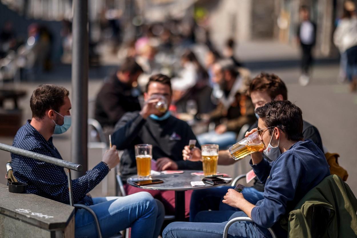 Tineri care se bucură de o bere și joacă cărți în timp ce terasele au fost redeschise